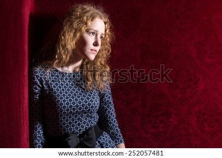 Portrait of sad, depressed, stressed, thoughtful young woman, full of worries, looking aside,  isolated on red background. Human face expressions, emotions, feelings, reaction, attitude - stock photo