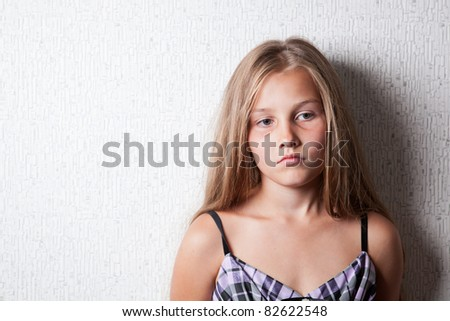 Portrait of sad girl at the wall, indoor - stock photo