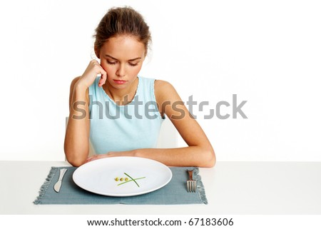 Portrait of sad girl looking at peas and leeks on plate - stock photo