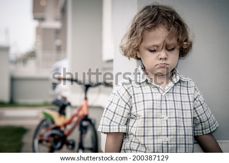 Portrait of sad little boy standing near house at the day time - stock photo
