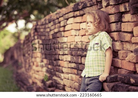 Portrait of sad little boy standing near the wall at the day time - stock photo