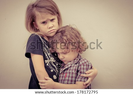 Portrait of sad little girl and little boy standing near wall in the day time - stock photo