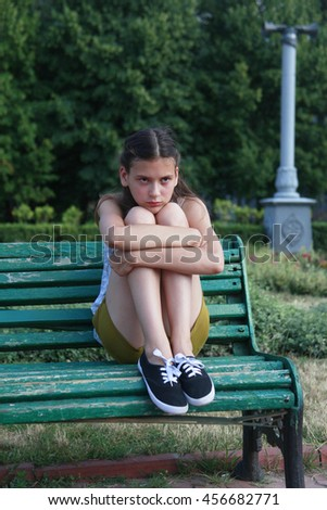 Portrait of sad little girl sitting on bench at the day time. - stock photo