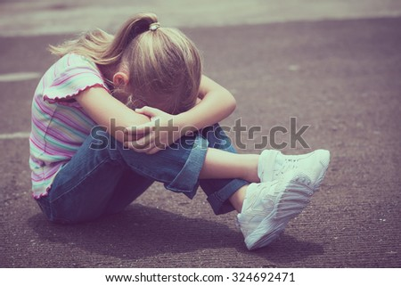 Portrait of sad little girl sitting on road at the day time. - stock photo