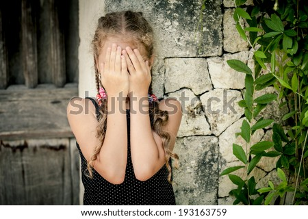 Portrait of sad little girl standing near stone wall at the day time - stock photo