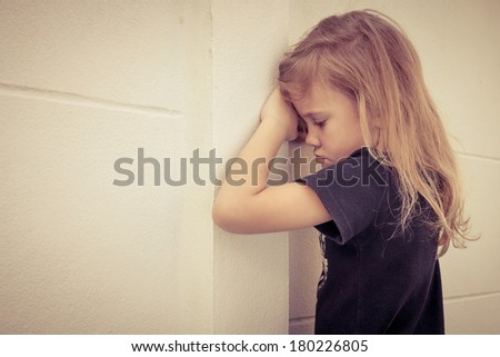 Portrait of sad little girl standing near wall in the day time - stock photo