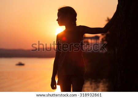 Portrait of sad little girl standing on the beach at sunset time. - stock photo