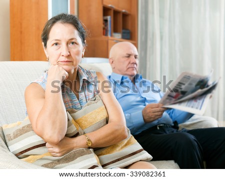 Portrait of sad mature woman near elderly man with newspaper at home - stock photo