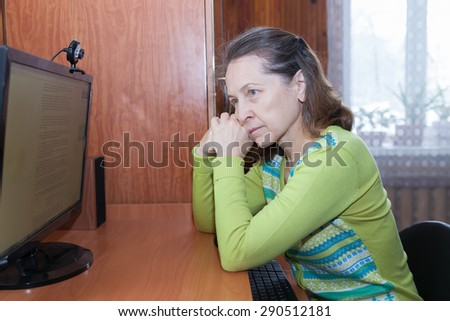 Portrait of  sad middle-aged woman near home computer