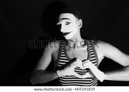 Portrait of sad mime with heart on black background