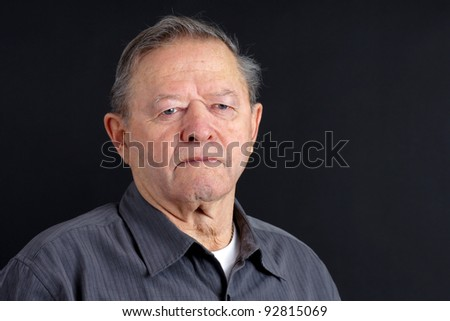 Portrait of sad or depressed senior man looking down over dark background, great details. - stock photo