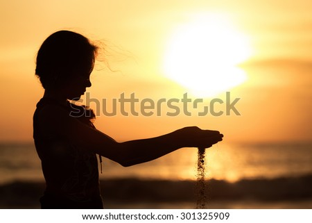 Portrait of sad teenager girl standing on the beach at sunset time. - stock photo