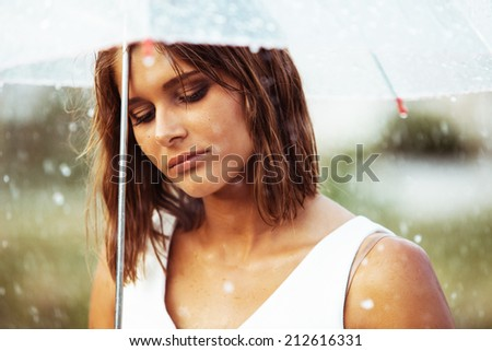 Portrait of sad young girl walking with umbrella under rain - stock photo