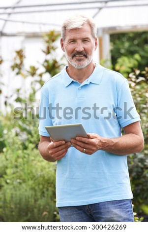 Portrait Of Sales Assistant In Garden Center With Digital Tablet - stock photo