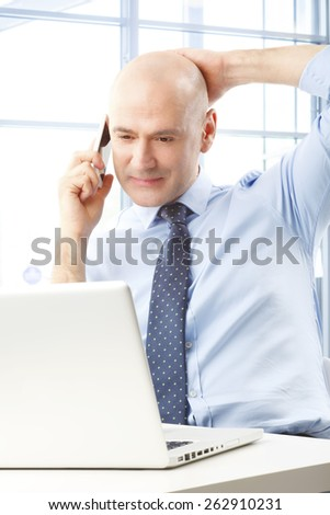 Portrait of sales man working at office while reading business report on laptop while making a call on mobile phone - stock photo
