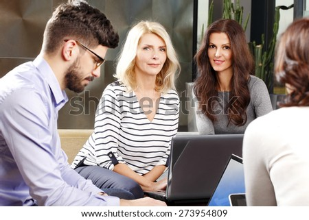 Portrait of sales team sitting at office and working with laptop on financial project. Mature businesswomen looking at camera and smiling.  - stock photo