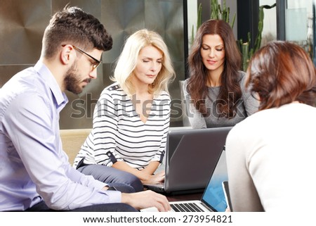 Portrait of sales team sitting at office and working with laptop on financial project. Mature businesswoman using her laptop.  - stock photo