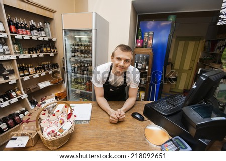 Portrait of salesman leaning at cash counter in supermarket - stock photo