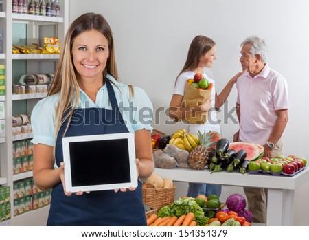 Portrait of saleswoman displaying digital tablet with father and daughter communicating in background - stock photo