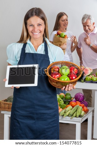 Portrait of saleswoman holding digital tablet and fruits basket with people shopping in background - stock photo