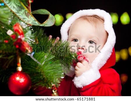 Portrait of Santa baby beside Christmas tree - stock photo