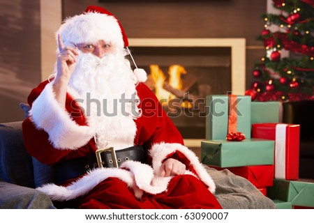 Portrait of Santa Claus by fireplace raising pointing finger, looking at camera.?