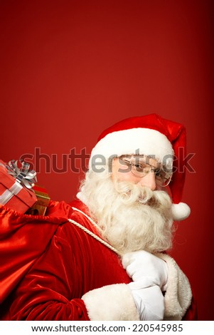 Portrait of Santa Claus carrying sack with gifts and looking at camera - stock photo