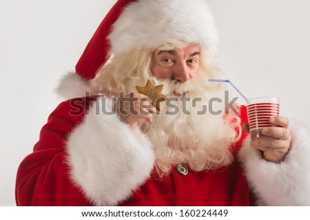 Portrait of Santa Claus Drinking milk from glass and holding cookie. Greeting card background