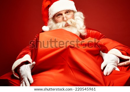 Portrait of Santa Claus embracing gigantic sack with gifts - stock photo