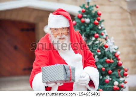 Portrait of Santa Claus giving Christmas present against house - stock photo