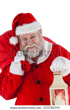 Portrait of santa claus holding christmas bag and lantern against white background