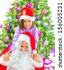 Portrait of Santa Claus holding on back cute little girl, beautiful decorated Christmas tree, New Year child's party, winter holidays concept - stock photo
