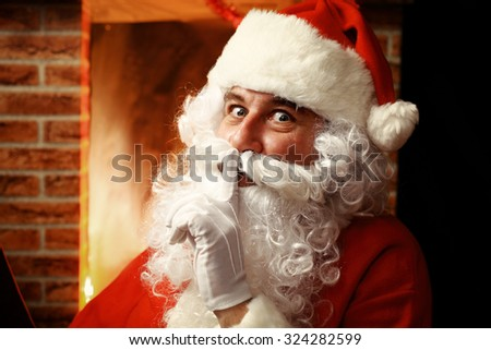 Portrait of Santa Claus keeping forefinger by his mouth - stock photo