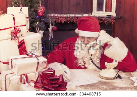 portrait of santa claus on the phone at his home compiles the wishlist for christmas - stock photo