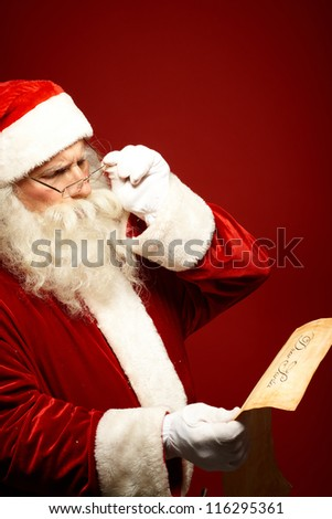 Portrait of Santa Claus reading Christmas letter in his hands - stock photo