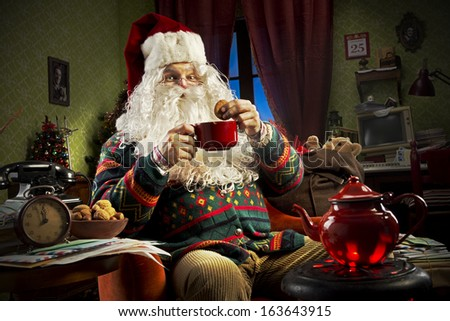 Portrait of Santa Claus sitting on armchair holding a cup of tea - stock photo