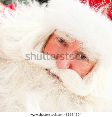 Portrait of Santa Claus standing outdoors. Snow falls. Natural light - stock photo