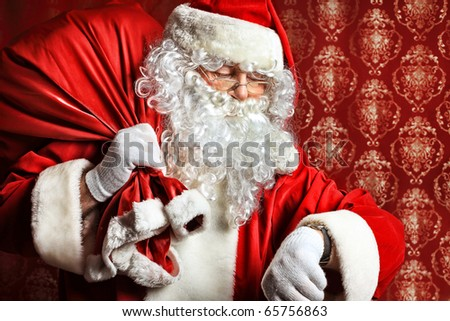 Portrait of Santa Claus with a bag of presents and looking at his watch. Christmas. - stock photo