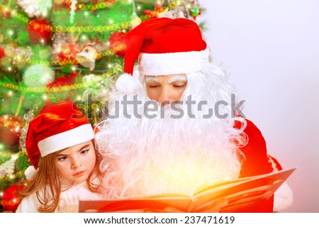 Portrait of Santa Claus with cute granddaughter sitting near Christmas tree, studio shot, reading magic book, celebrating winter holidays - stock photo