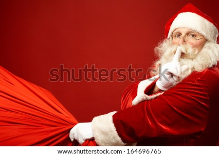 Portrait of Santa Claus with huge red sack keeping forefinger by his mouth and looking at camera - stock photo