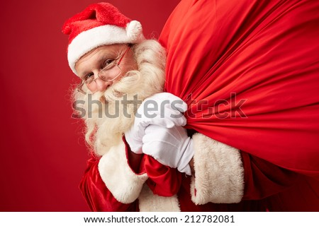 Portrait of Santa Claus with huge sack looking at camera - stock photo