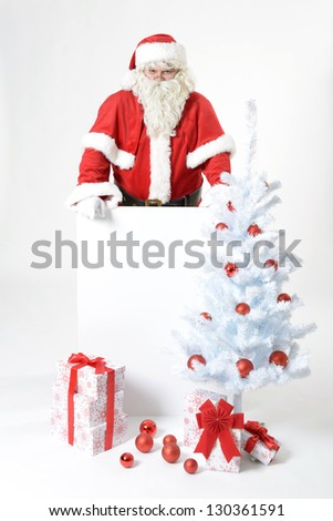 portrait of santa clause behind an advertising board - stock photo