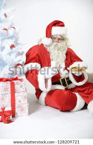portrait of santa clause takes a break with milk and cookies - stock photo