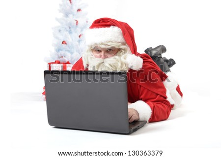 portrait of santa clause with laptop - stock photo