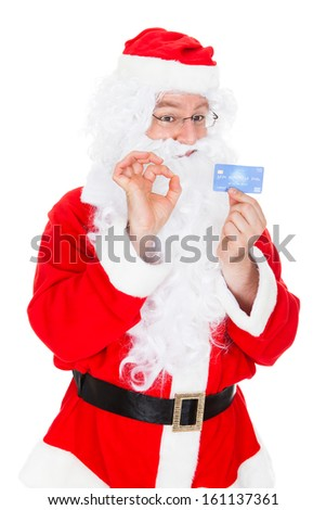 Portrait of santa pointing at credit card over white background - stock photo