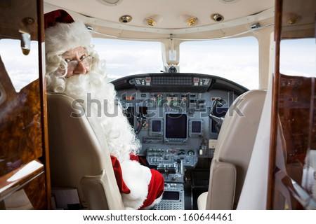 Portrait of Santa sitting in cockpit of private jet - stock photo