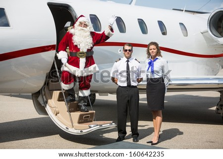 Portrait of Santa waving hand on private jet's ladder while pilot and airhostess standing by - stock photo