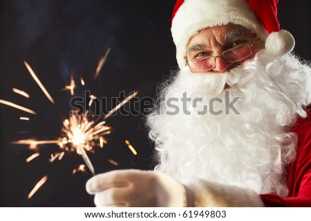 Portrait of Santa with a burning stick of dynamite isolated on black - stock photo