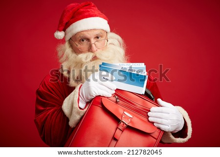 Portrait of Santa with airline tickets and red leather briefcase looking at camera