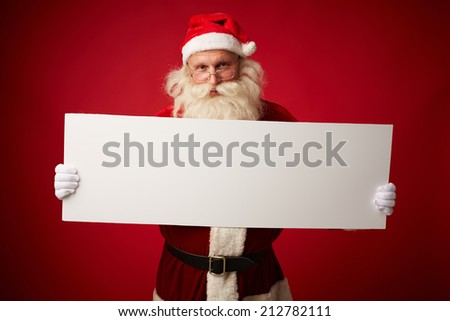 Portrait of Santa with blank paper looking at camera - stock photo